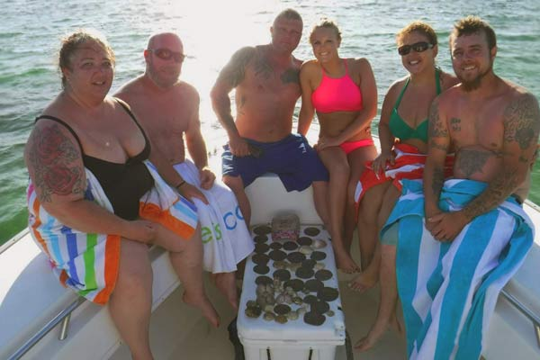 Photo of a group that rented a Pontoon boat and went to Shell Island. They are at the end of the boat and around the shells they collected from their trip