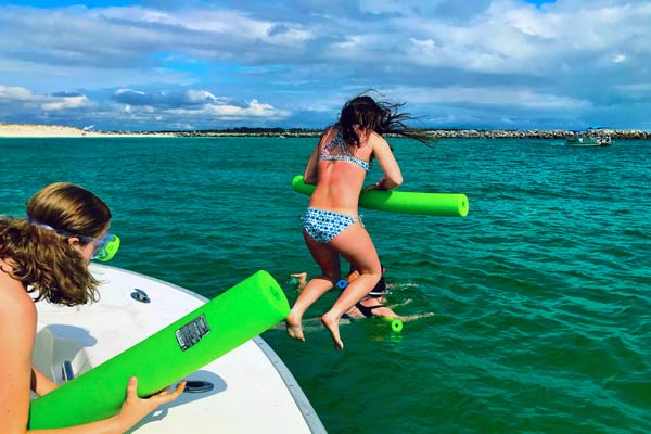 Image of girl jumping off the side of a anchored Pontoon boat with a pool noodle to go swimming with the dolphins