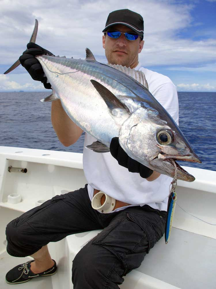 Man sitting on edge of boat holding up big tuna he caught on his fishing charter