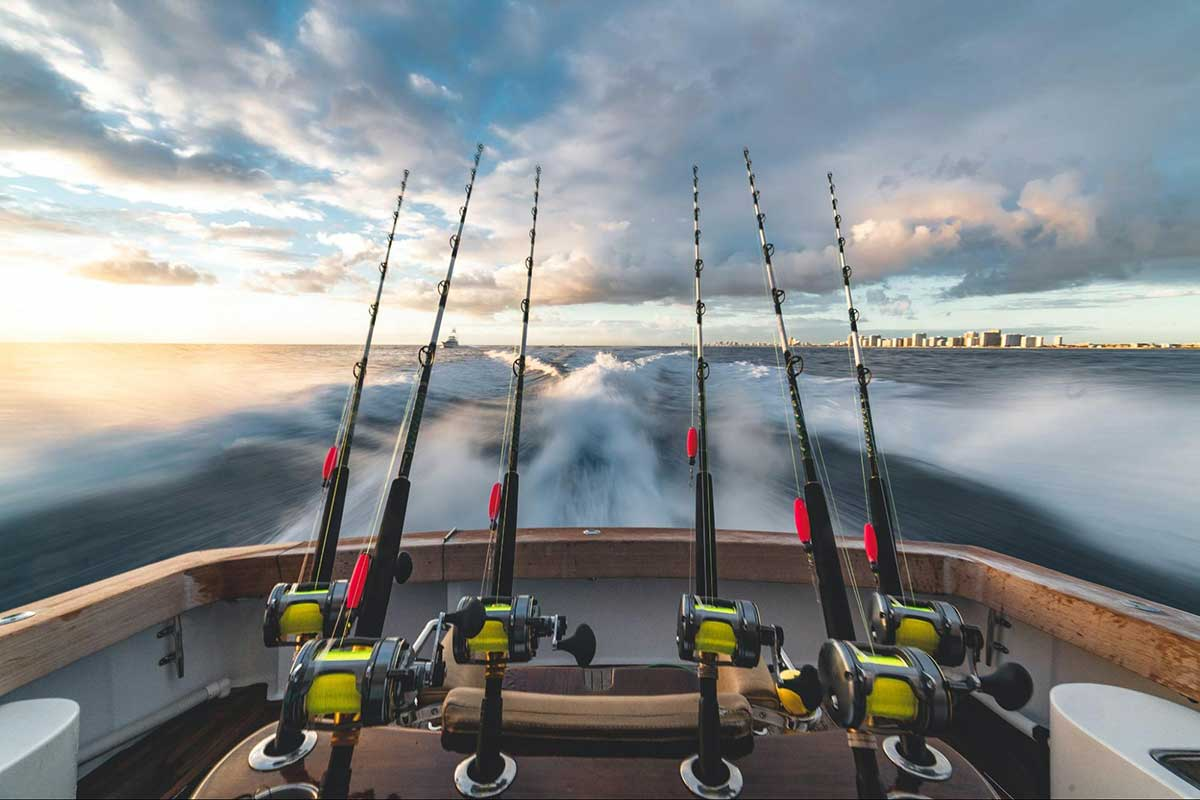 Photo of fishing boat taken from the bow, facing the stern. The back of the boat is visible with 6 fishing poles and the wake of the boat is blurry from the speed. The sky is partly cloudy and looks expansive and beautiful.