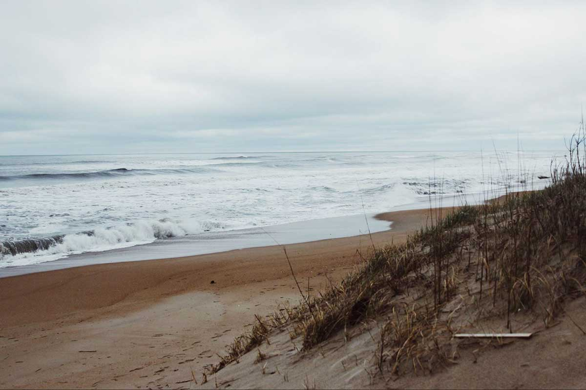 Image of an empty beach near Shell Island. The water is calm and the sky is overcast. The beach is part sanctuary for wildlife.