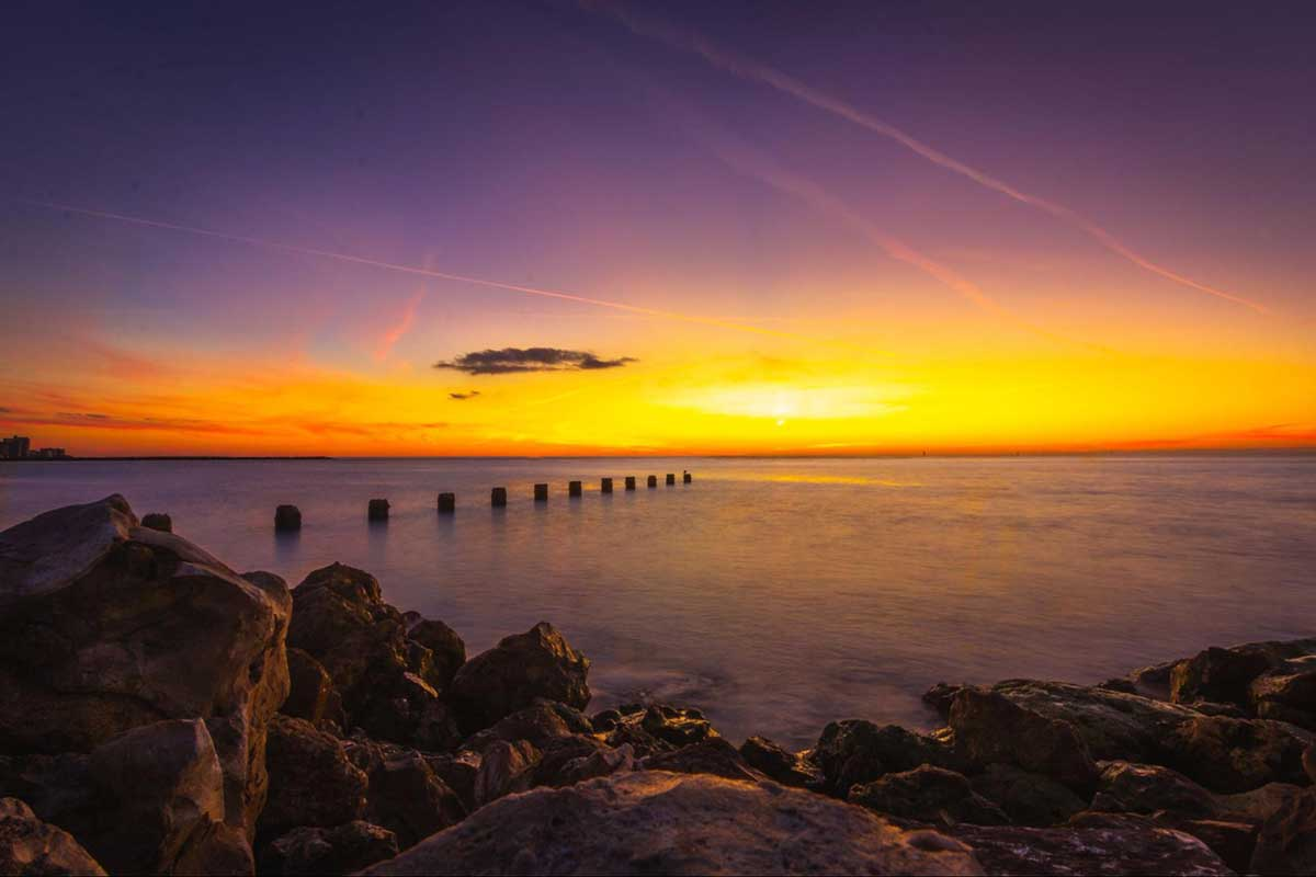 Photo from a rocky beach of sunset over the water. The sun is already rising a bit. The water is calm with wooden posts in the water in a straight line.