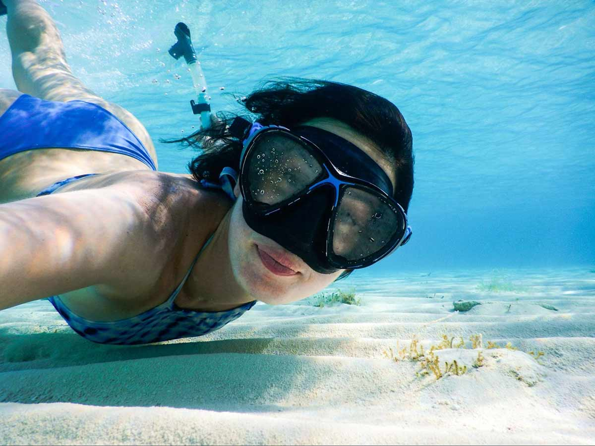 Image of woman snorkeling in the clear ocean blue water. She's close to the sandy sea floor and is facing the camera. She has a happy and contented look on her face.