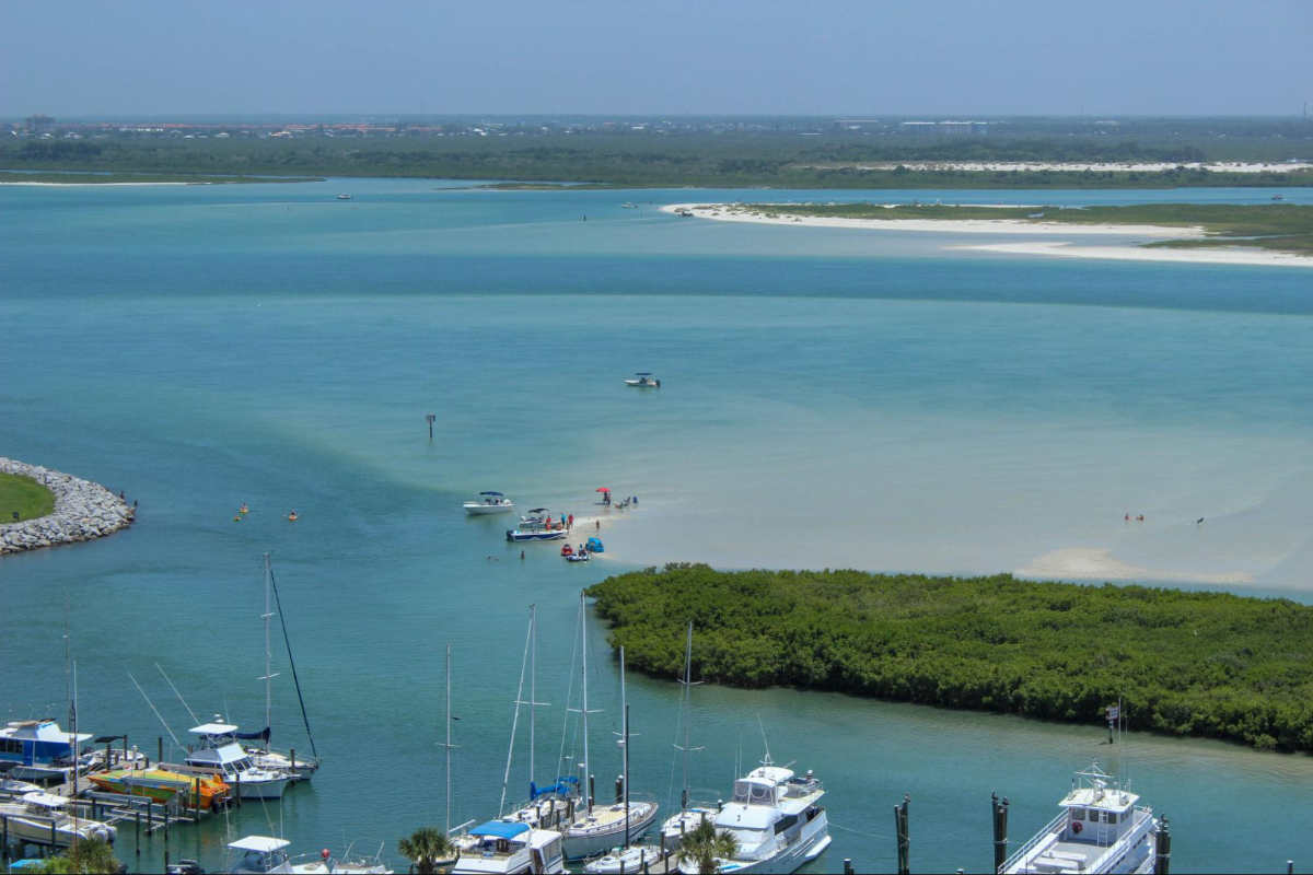 Aerial photo of boats at a marina at an inlet. There is a sandbar by one of the barrier reefs where people are standing in the water.