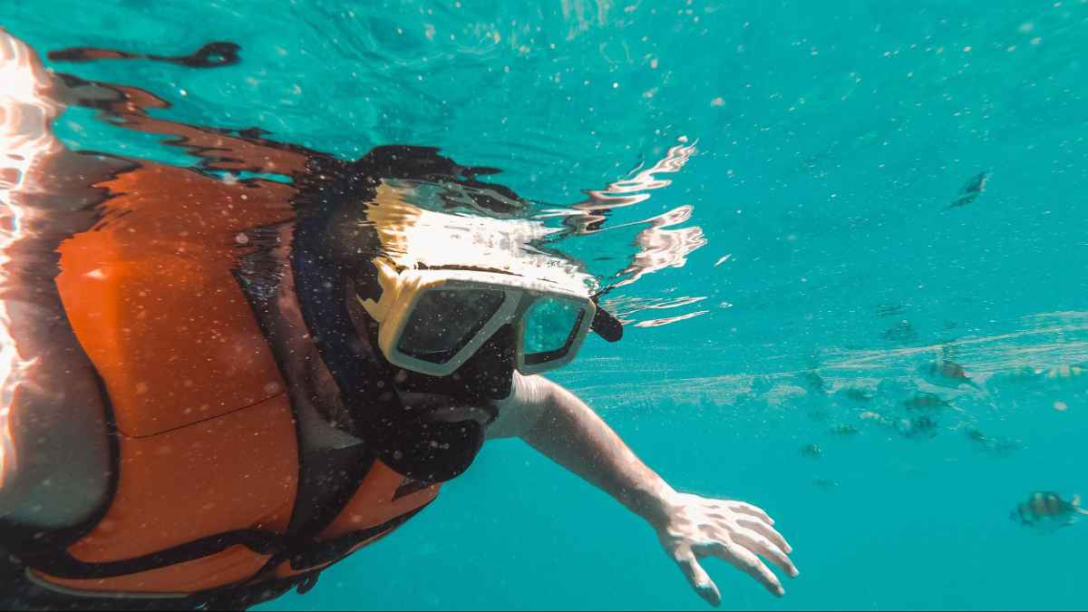 Man swimming with snorkeling gear in the ocean. The water is a beautiful turquoise blue.