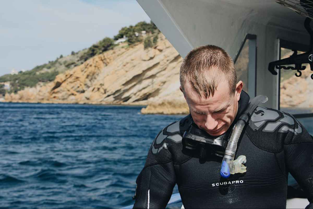 Man with professional SCUBA suit wearing snorkeling gear. He is on a boat in the water near an island.