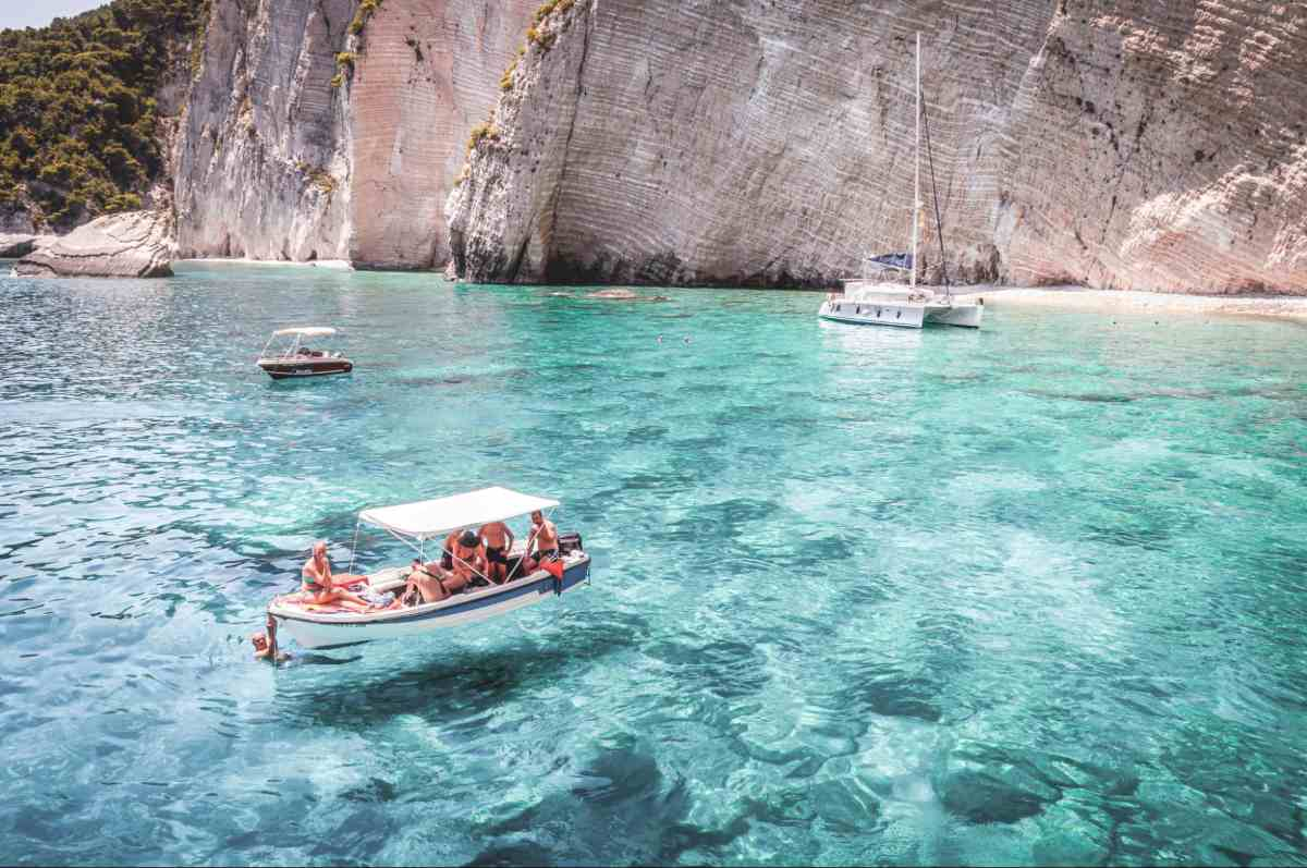 Photo of pontoon boats anchored by an island that has very steep rock cliffs.