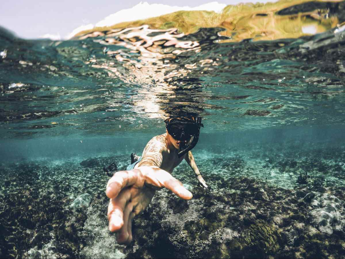 Photo of young man snorkeling. The photo is shot from half in the water and half out. The boy's hand is extended as if to grab something towards the camera.